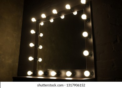 Antique mirror with lamps close up on black background