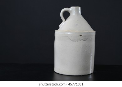 Antique moonshine jug fired with a white glaze.