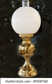 antique oil lamp with white lampshade isolated on a texture background