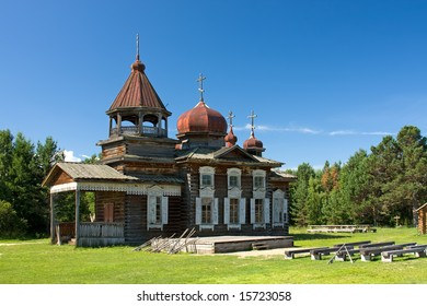 Antique old russian wooden church in the green forest