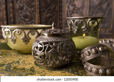 Antique Omani silver container and serviette holders with candle holders faded out in the background.