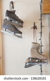Antique pair of men's and women's ice skates hanging on the wall.
