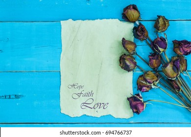 Antique parchment paper letter with the words Hope, Faith, Love and vintage dried roses border on rustic teal blue wood background; religious background with copy space