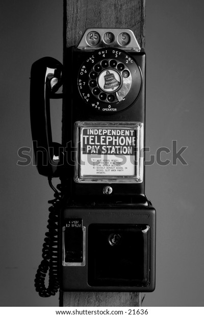 Antique pay telephone with dial mounted on wooden pole