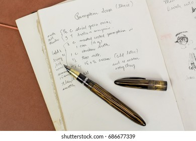 Antique pen on top of a handwritten pumpkin soup recipe
