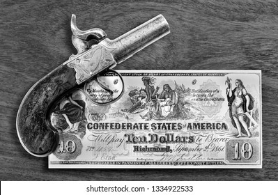 Antique percussion pistol and 1861 Confederate ten dollar bill in black and white.