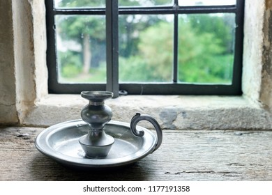 Antique pewter candle holder in front of window with garden in distance