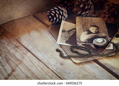 antique photos and old locket on wooden table. filtered image. selective focus