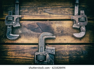 Antique pipe wrenches on a rough wood background