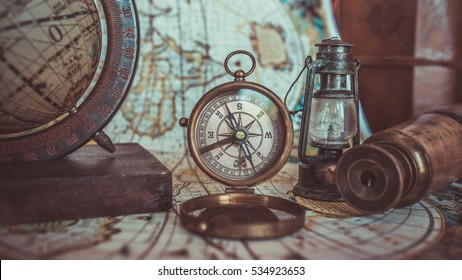 Antique pirate rare items collections including with a brass pocket compass with cover lid, retro oil lamp, telescope, globe model rotation on a wooden base on ancient world map. (vintage style)