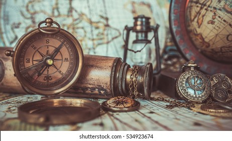 Antique pirate rare items collections including with a bronze pocket compass with cover lid, old binoculars, compass necklace, world globe base on ancient world map background.  (vintage style)