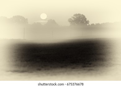 Antique plate photography of rising morning sun over misty rural landscape.