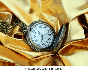 Antique pocket watch on a gold background closeup