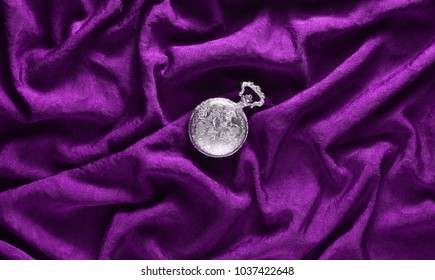 Antique  pocket watch on a violet silk background. Top view.