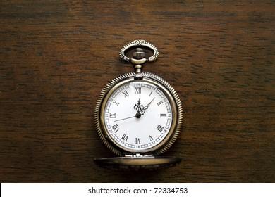 Antique pocket watch on a wood board
