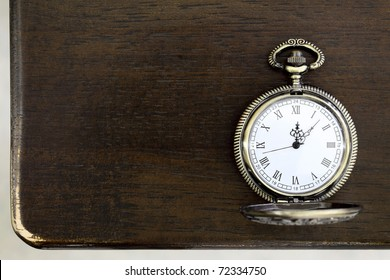 Antique pocket watch on a wooden table