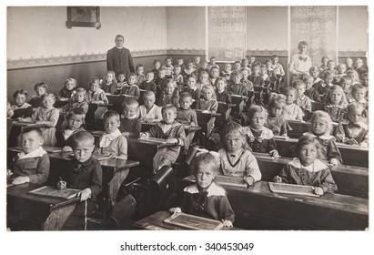 Antique portrait of school classmates. Group of children and teachers. Vintage picture with original film grain and blur