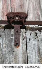 Antique rusty rail hardware still holds up an oaken barn door on a farm that's no longer used