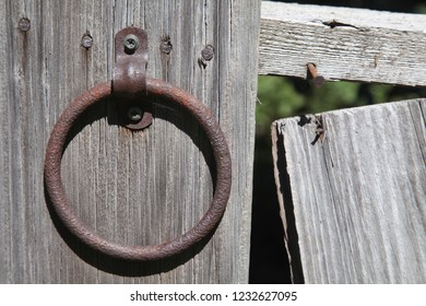 An antique, rusty ring on the side of a barn, still waiting for the horse reins that it used to hold, when the farm was still in use.