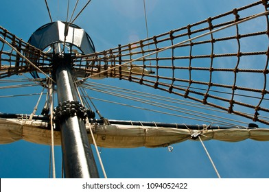 Antique sailing ship mast crows nest with rigging against blue sky