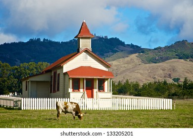 Antique school house sits in a meadow beneath the rolling hills of the central California coast.