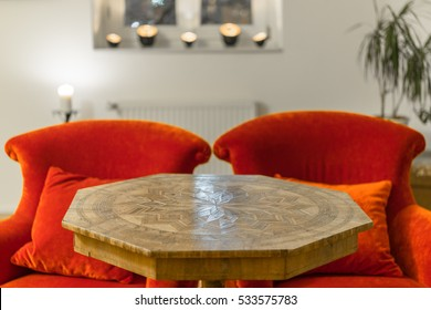 Antique side table with intarsia and red chair