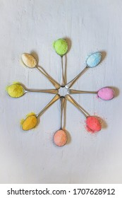 Antique silver spoons laid out in patterns holding brightly rainbow colored jello powder, on a white textured background