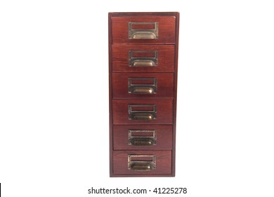 Antique six drawer oak library file card cabinet with brass label holders isolated over white background.