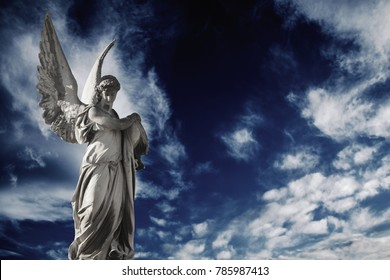 Antique sstatue of an angel on sky dark background