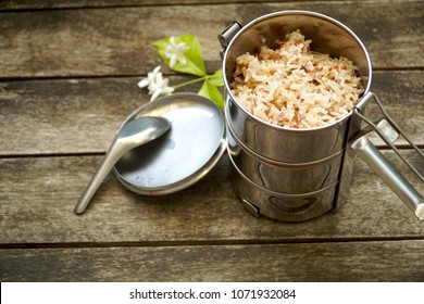 Antique stainless steel food carrier or Tiffin food container and spoon on wood background. Brown rice. Set breakfast or lunch. Still life food.