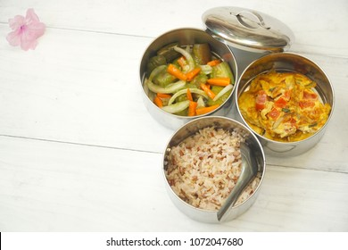Antique stainless steel food carrier (Tiffin food container) and spoon on wood background. Brown rice, Spicy salad long eggplant, carrot and Omelette (Omelet). Set breakfast or lunch. Still life food.