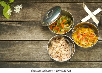 Antique stainless steel food carrier (Tiffin food container) and spoon on wood background. Brown rice /Spicy salad long eggplant, carrot and Omelette (Omelet). Set breakfast or lunch. Still life food.