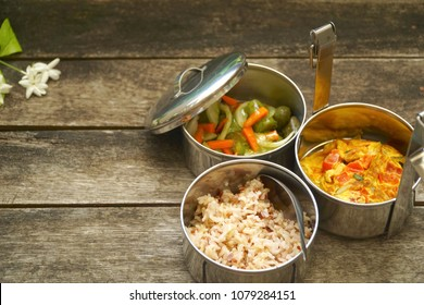 Antique stainless steel food carrier (Tiffin food container) and spoon on wood background. Set of food. Brown rice, Spicy salad long eggplant, carrot and Omelette (Omelet). Copy space. Simple life.