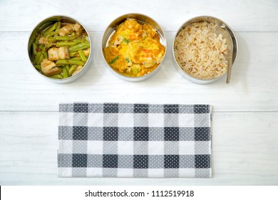 Antique stainless steel food carrier (Tiffin food container) on wood background. Stir fried string bean and pork, Omelette with shrimp (Omelet), Brown rice. Simple style. Copy space.