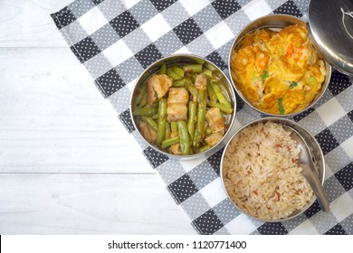 Antique stainless steel food carrier (Tiffin food container) and spoon on wood background. Set of food. Brown rice, Stir fried string bean and pork, Omelette with shrimp (Omelet). Copy space. Simple.