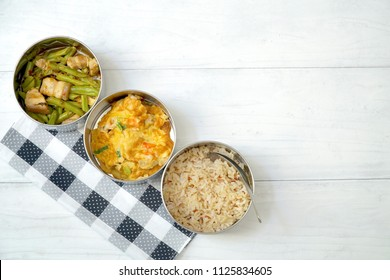 Antique stainless steel food carrier (Tiffin food container), spoon on wood background. Brown rice, Stir fried string bean and pork, Omelette with shrimp (Omelet). Simple style. Slow life. Copy space.