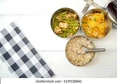 Antique stainless steel food carrier (Tiffin food container) on wood background. Brown rice in spoon, Stir fried string bean and pork, Omelette with shrimp (Omelet). Simple style.Slow life. Copy space