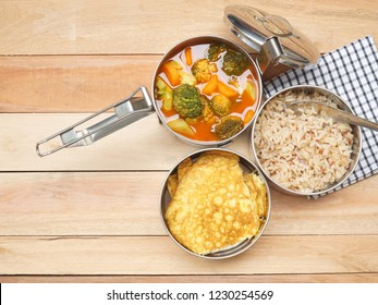 Antique stainless steel food carrier (Tiffin food container) and spoon on wood table. Omelette (Omelet), Vegetable Sour soup and Brown rice. Set of food. Still life. Simple lifestyle.
