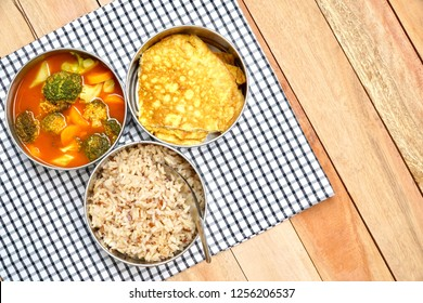 Antique stainless steel food carrier (Tiffin food container) and spoon on wood table. Omelette (Omelet), Vegetable sour soup and Brown rice. Set of food. Lifestyle. Copy space.