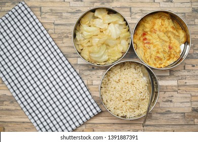 Antique stainless steel food carrier (Tiffin food container) and spoon on wood table. Omelette (Omelet), Stir fried cabbage and rice. Still life food. Simple style. Free space for any text.