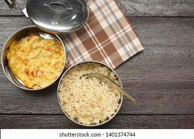 Antique stainless steel food carrier (Tiffin container) and spoon on tartan fabric. Omelette (Omelet). Still life. Simple style. Free space for any text.