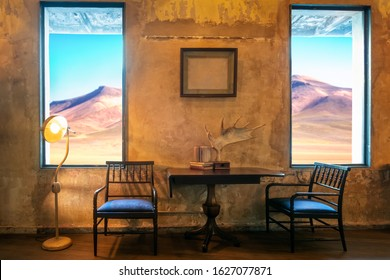 Antique standing lamp inside a rustic living area / patio decorated with old books, deer horn and picture frame inside a grunge cement wall room with giant windows with desert mountain view.