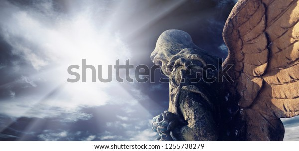 Antique statue of wonderful angel in the rays of the sun. Architecture, archetype, religion, faith concept.