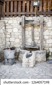 Antique stone fixture with a millstone and a press for squeezing extra virgin olive oil of the first cold press