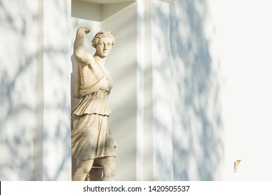 Antique stone sculpture of the goddess of hunting and fertility Artemis in the niche of the palace building in the park. Culture and art of ancient Greece. The statue of a woman hunter.