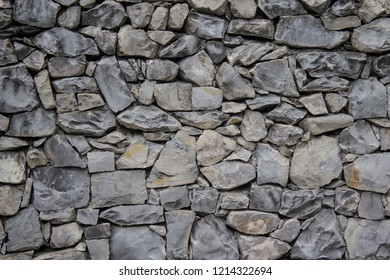 Antique stone wall hand-made. Background, texture, wallpaper.