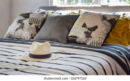 antique straw hat on black and white patterned bed at home