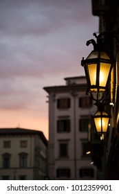 Antique street lamp in Florence, Italy, with dramatic evening sky and old buildings on bokeh background.