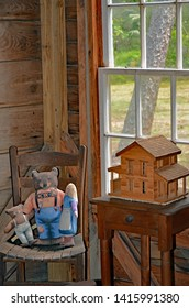 Antique stuffed toys of Goldilocks and the three bears sitting on a childs chair next to a handmade wooden dollhouse on a table set in the corner before a sunny window in a wood cabin.