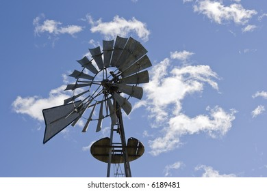 Antique style windmill against a blue sky with clouds.